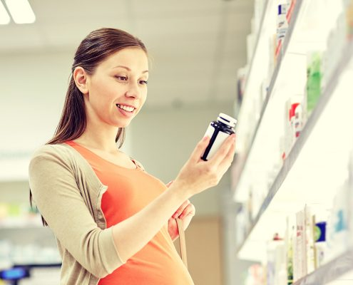 Woman looking at product ingredients for certification safety & efficacy